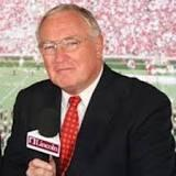 headshot of Dave Rowe presenting at football game with mic in hand